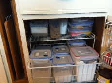 I hunted until I found a wire shelf that, with a little encouragement, would fit inside this cupboard for stacking smaller containers above the larger ones.  A large wire bin that fits under the shelf allows me to pull out all the flours at once to get at what I need.