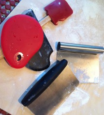 Two dough scrapers, a rubber scraper with notches that are good at cleaning dough off beaters and edges of bowls, etc.,and two bench scrapers.  One of the bench scrapers has measurements engraved which is handy sometimes.